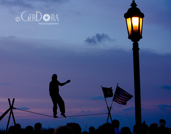 Silhouette of a man walking on a tightrope before a crowd with the backdrop of a sunset and a lamp post in the foreground in the Florida Keys