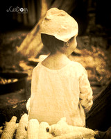 sepia tone photo of little girl in colonial times attire at Claude Moore Farm Virginia